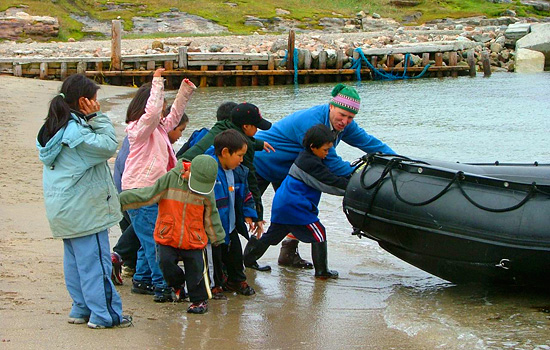 Local children help a man push a boat in to the water