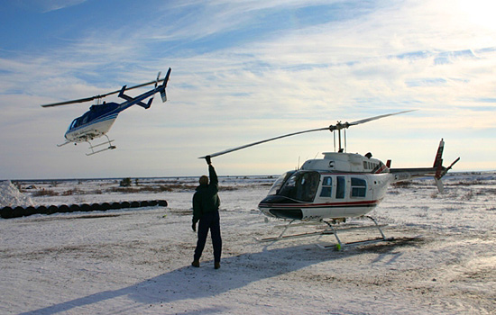 A man stands in front of a helicopter as another is mid flight over the arctic tundra