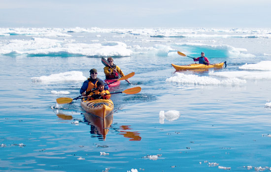 Kayakers explore icebergs on a small guided tour